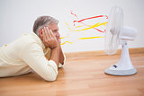 Man lying on floor looking at fan