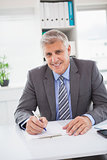 Smiling businessman writing on clipboard