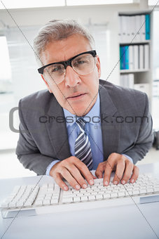 Focused businessman typing at his desk