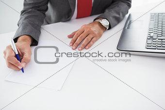 Mature businessman writing on document