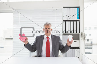 Mature businessman holding coffee and piggy bank