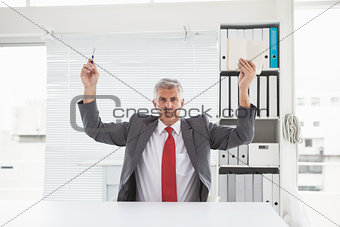 Mature businessman holding pen and book