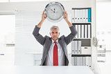 Mature businessman holding large clock