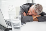 Mature businessman sleeping on desk