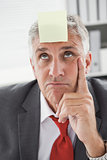Confused businessman with sticky note on head