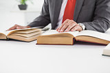 Businessman sitting at desk reading books