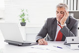 Tired businessman falling asleep at desk