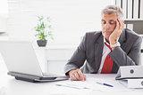 Tired businessman falling asleep at desk