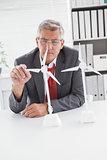 Businessman looking at model wind turbines