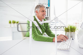 Casual businessman working with model wind turbines