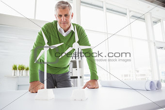 Casual businessman looking at model wind turbines