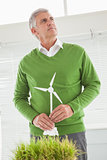 Casual businessman holding model wind turbine