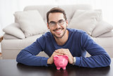 Smiling young man with piggy bank