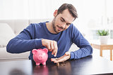 Young man putting coins in piggy bank