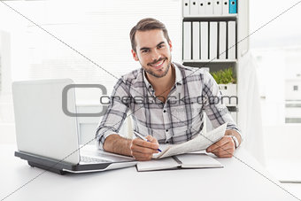 Casual businessman writing on newspaper