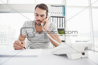 Casual businessman writing and phoning at his desk