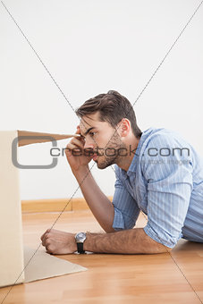 Casual man looking inside cardboard box
