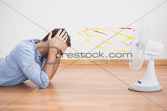 Casual man lying in front of fan