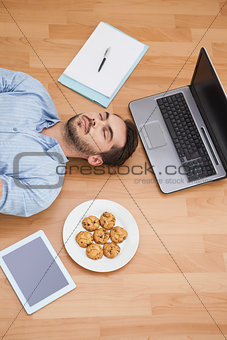 Casual man lying on floor surrounded by his possesions