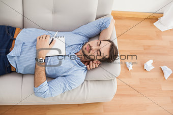 Casual man lying on couch with crumpled papers