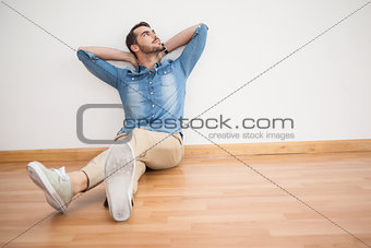 Casual man sitting on floor looking up