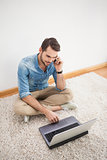 Casual man sitting on floor using laptop on the phone