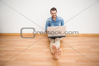 Casual man sitting on floor using laptop
