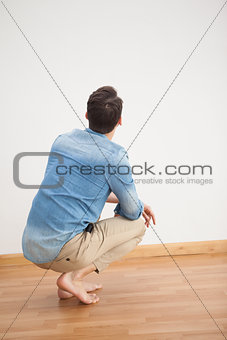 Casual man crouching on floor looking at wall
