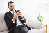 Businessman sending a text on the couch