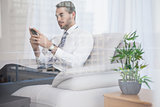 Businessman texting on his couch seen through glass