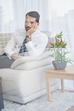 Businessman sitting on his couch seen through glass