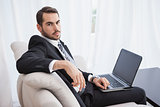 Businessman using laptop on his couch