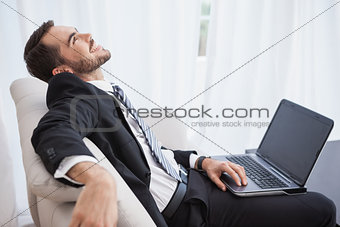 Smiling businessman using laptop on his couch