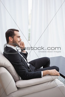 Smiling businessman making a call on his couch
