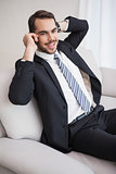 Businessman making a call on his couch