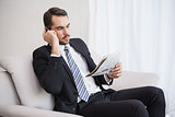 Businessman making a call on his couch reading newspaper