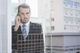 Businessman looking out window on the phone