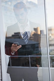 Businessman sending a text seen through window