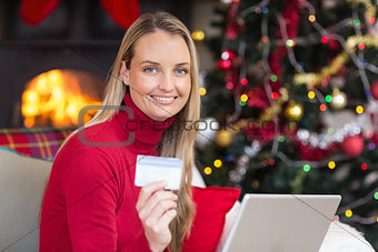 Blonde shopping online with laptop at christmas