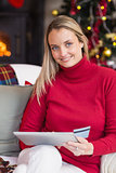 Festive blonde woman using her credit card and tablet pc