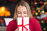 Pretty blonde woman holding christmas gift