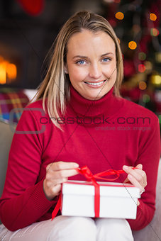 Blonde opening christmas gift while smiling at camera