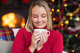 Pretty blonde enjoying a hot drink at christmas