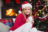 Smiling blonde holding a mug of hot chocolate at christmas