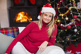 Happy blonde relaxing on the couch at christmas