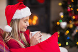 Smiling blonde wearing santa hat while holding a mug