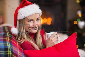 Smiling blonde wearing santa hat while holding a mug