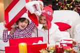 Festive little siblings opening a gift