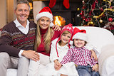 Portrait of a smiling family sitting on sofa at christmas time