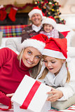 Surprised mother and daughter opening a christmas gift